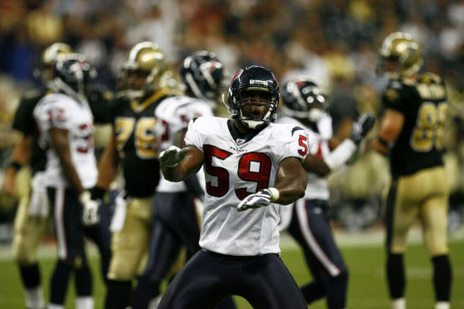 Texans linebacker DeMeco Ryans helps keep the Saints from making an extra-point attempt in the second quarter. Photo: Michael Paulsen, Chronicle