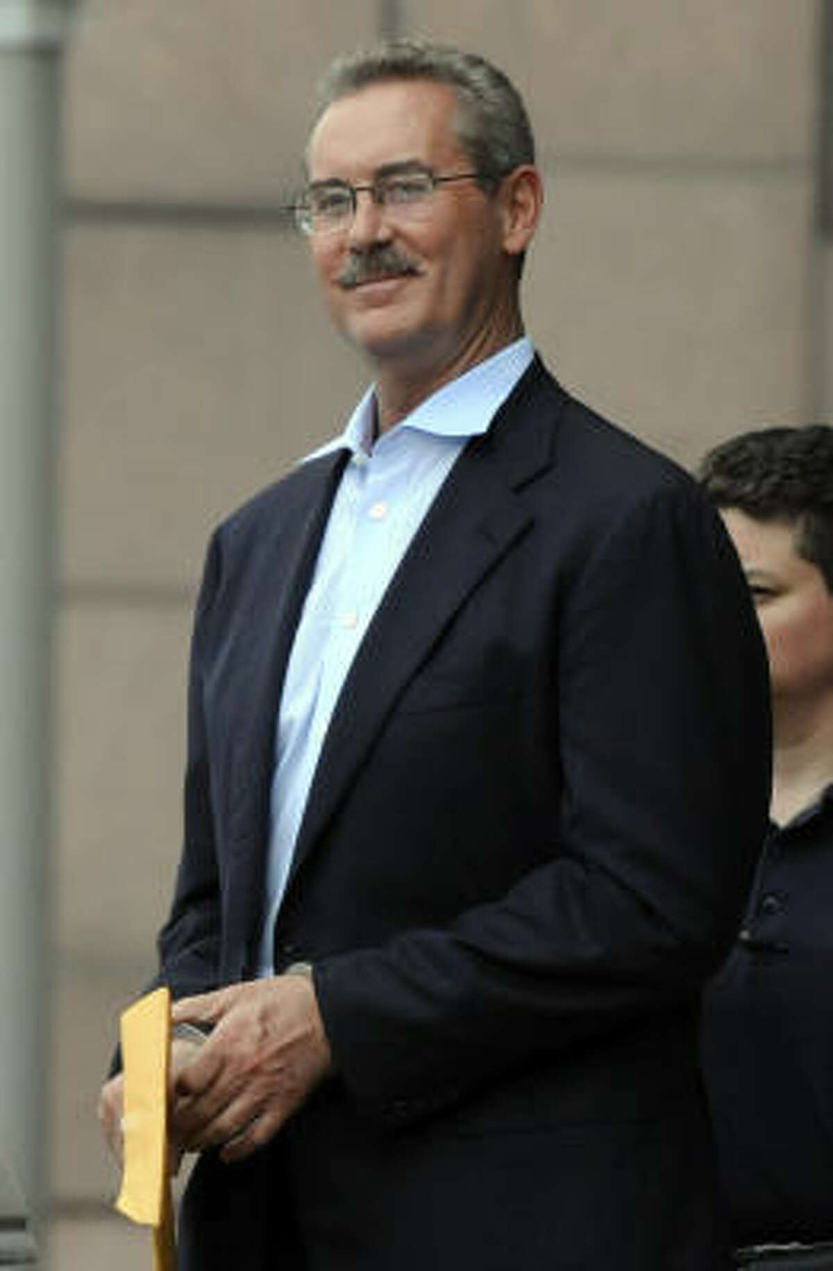 R. Allen Stanford smiles as he is escorted out of the federal courthouse in Houston in June.