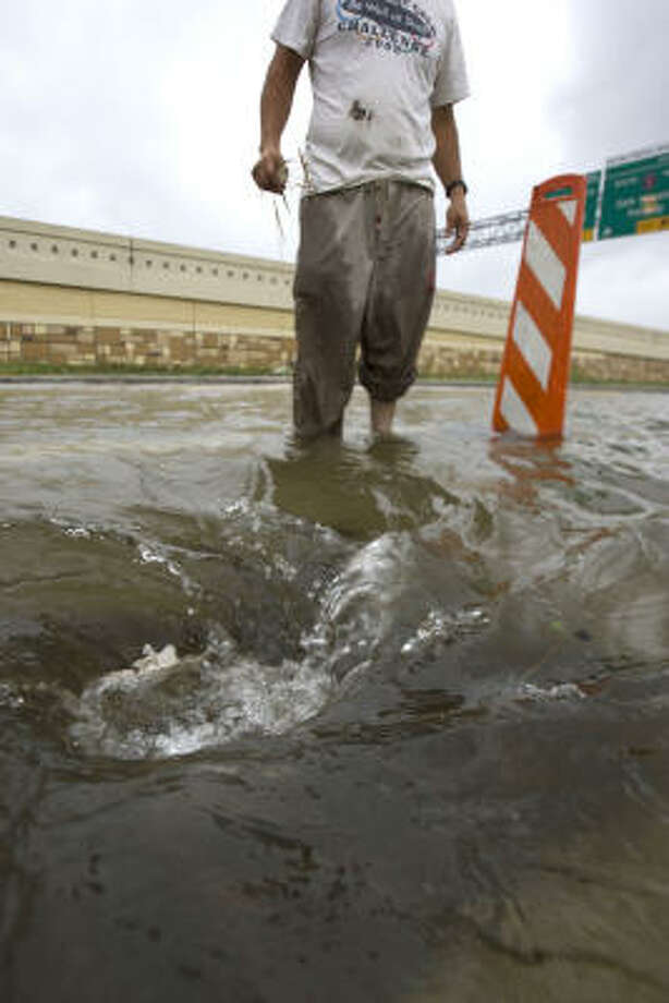 Jose Mendoza clears a drain near Interstate 10 at Gessner. Photo: Johnny Hanson, Chronicle