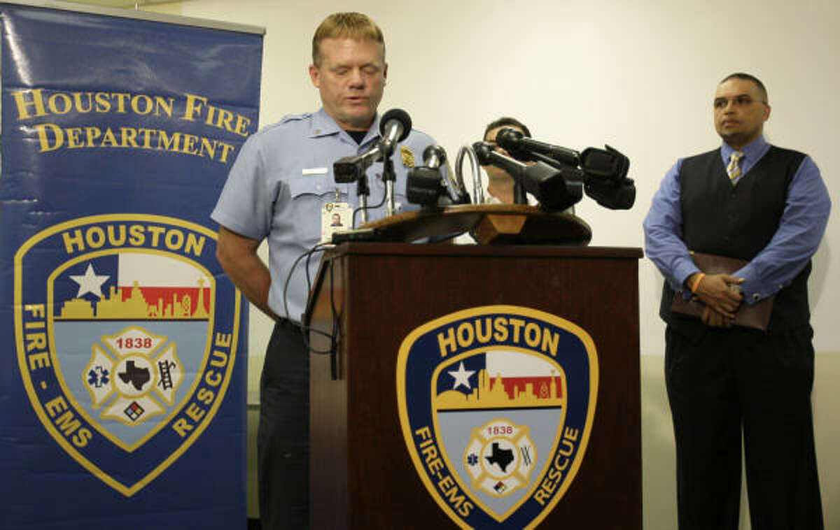 As Houston Fire Capt. Keith Smith, left, appears at HFD headquarters Monday, the Rev. D.Z. Cofield, vice president of the NAACP's Houston chapter, waits to speak on Smith's behalf.
