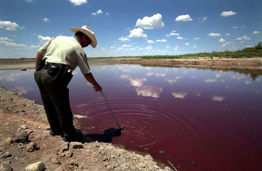Texas State Park police officer Thomas Bigham reaches down into what remains of O.C. Fisher Lake Wednesday, Aug. 3, 2011, in San Angelo, Texas. A bacteria called Chromatiaceae has turned the 1-to-2 acres of lake water remaining the color red. A combination of the long periods of 100 plus degree days and the lack of rain in the drought -stricken region has dried up the lake that once spanned over 5400 acres. (AP Photo/Tony Gutierrez) Photo: Tony Gutierrez, STF