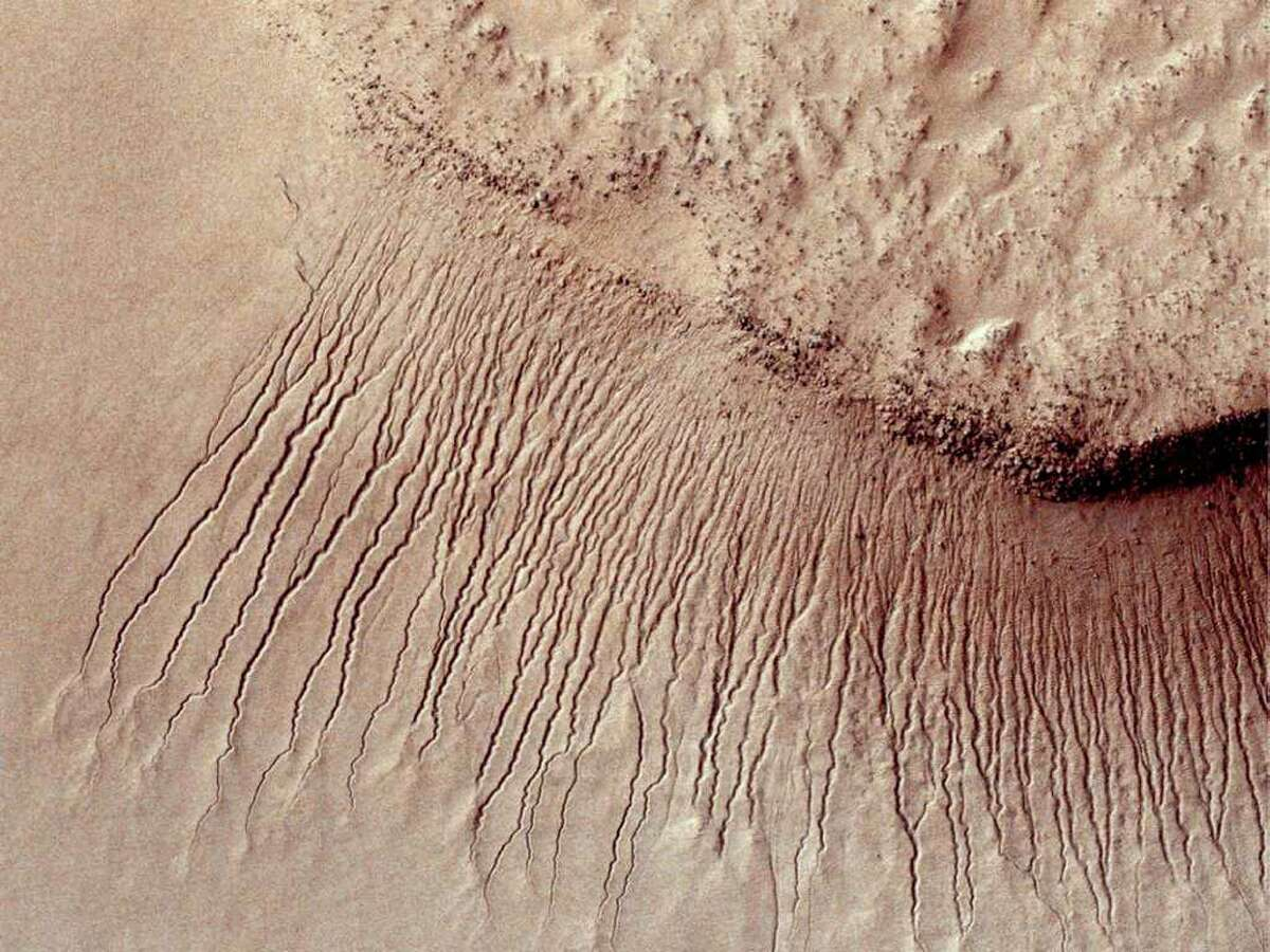 """This January 14, 2011 image from the High Resolution Imaging Science Experiment (HiRISE) camera on NASA's Mars Reconnaissance Orbiter show portions of the Martian surface in unprecedented detail. This one shows many channels from 1 meter to 10 meters (approximately 3 feet to 33 feet) wide on a scarp in the Hellas impact basin. On Earth we would call these gullies. Some larger channels on Mars that are sometimes called gullies are big enough to be called ravines on Earth. Scientists have spotted dark stripes on some slopes on Mars in the warmer months, and they believe it may be evidence of flowing salt water, NASA researchers said on August 4, 2011. If confirmed, it would be the first discovery of active liquid water in the ground on Mars. Finger-like markings have shown up along several steep slopes in the middle latitudes of Mars' southern hemisphere, fading again once colder temperatures move in, according to data from NASA's Mars Reconnaissance Orbiter. AFP PHOTO/HO / NASA/JPL-Caltech/University of Arizona = RESTRICTED TO EDITORIAL USE - MANDATORY CREDIT """"AFP PHOTO / NASA/JPL-Caltech/University of Arizona """" - NO MARKETING NO ADVERTISING CAMPAIGNS - DISTRIBUTED AS A SERVICE TO CLIENTS = (Photo credit should read HO/AFP/Getty Images)"""