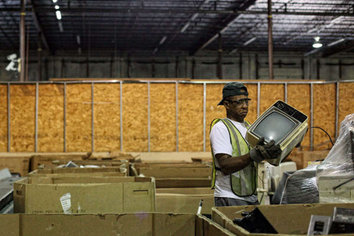 Howard Shields handles a discarded television Thursday at Houston electronics recycling company CompuCycle's processing facility.