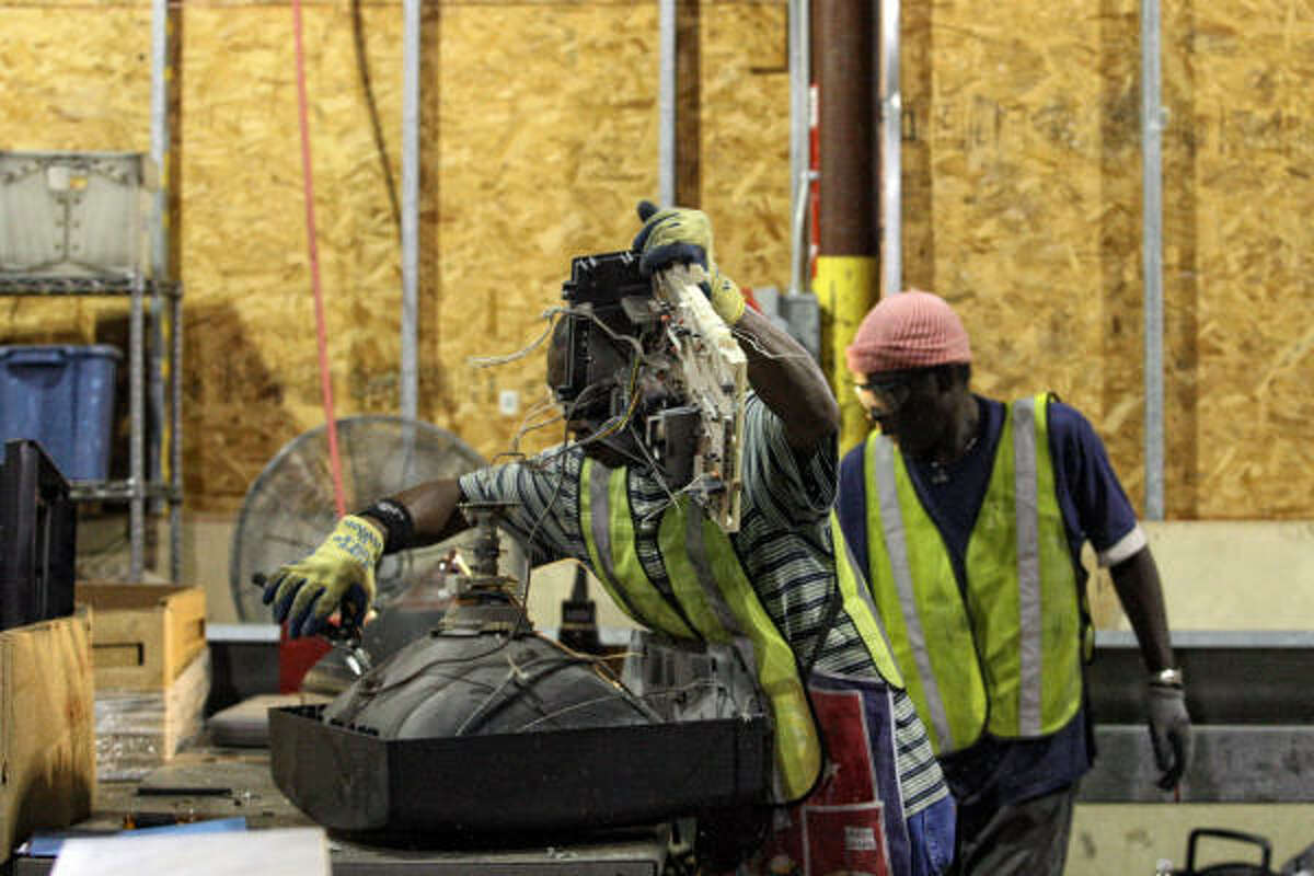 CompuCycle employees Matthew Albert, left, and Charles Henry take apart an old television Thursday.