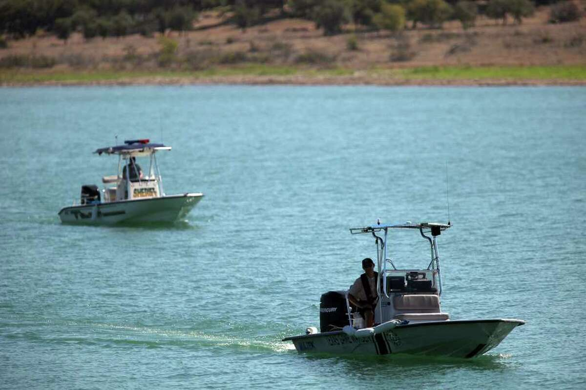 FILE PHOTO - Comal County Sheriff's Office Detective Rex Campbell, left, and Texas Game Warden Michael McCall, right, use side scan sonar equipment to search for the body of drowning victim at Canyon Lake on Thursday, August 4, 2011.