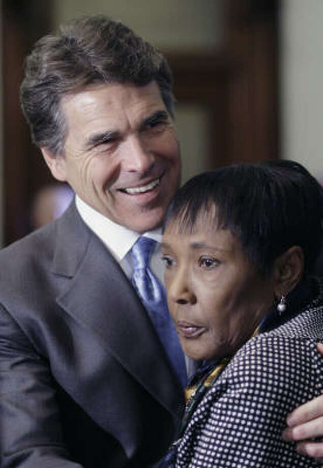 Gov. Rick Perry embraces Ruby Cole Session, whose son, Timothy Cole, died in prison while serving time for a rape he did not commit. Photo: Harry Cabluck, Associated Press