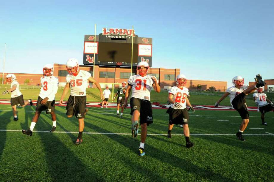 The Lamar University football team warms up on the field as the Cardinals hold their first practice of the season at  Provost Umphrey Stadium. Thursday, August  4, 2011.  Valentino Mauricio/The Enterprise