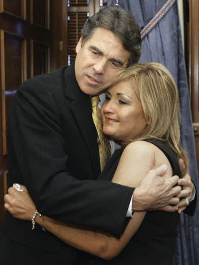 Texas Gov. Rick Perry embraces Helen Madla on Wednesday signing a bill to frees tuition revenue bonds for three new Texas A&M campuses and allow for the expansion of the Texas A&M University-Central Texas, Texas A&M University-San Antonio, and University of North Texas at Dallas. Mrs. Madla is wife of the late Sen. Frank Madla, D-San Antonio. Photo: Harry Cabluck, AP