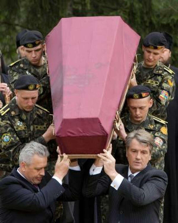 Ukrainian President Viktor Yushchenko, right, takes part in a ceremony for the re-burial of Soviet prisoners of war.