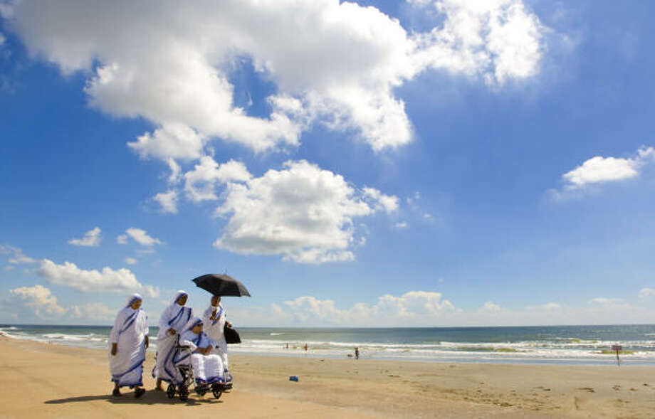 A group of Sisters of Mother Teresa of Calcutta's Missionaries of Charity walk along the Galveston Seawall Monday. Photo: Brett Coomer, Chronicle
