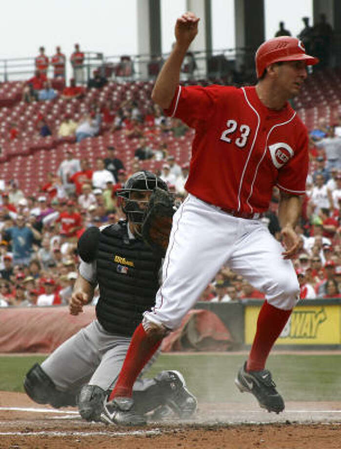 Cincinnati Reds' Adam Rosales scores on the play as Ivan Rodriguez sprained his left knee. Photo: David Kohl, AP
