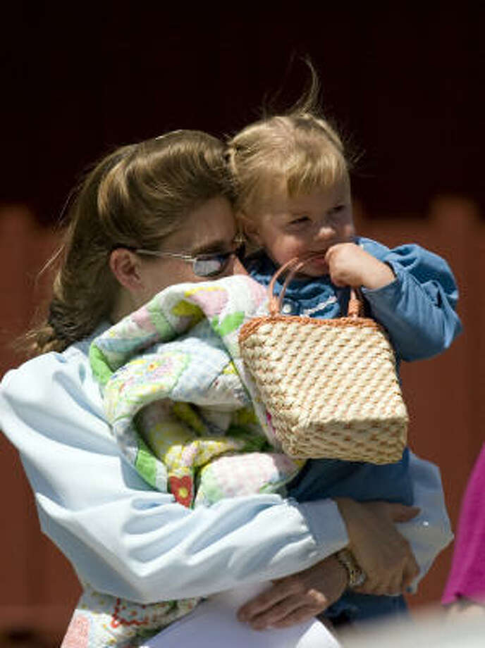 A mother from the Fundamentalist Church of Jesus Christ of Latter Day Saints reunites with her child at the Kidz Harbor facility in Liverpool, Texas, in June 2008. Two months earlier, CPS seized 439 children from the polygamist sect. Photo: Johnny Hanson, Chronicle
