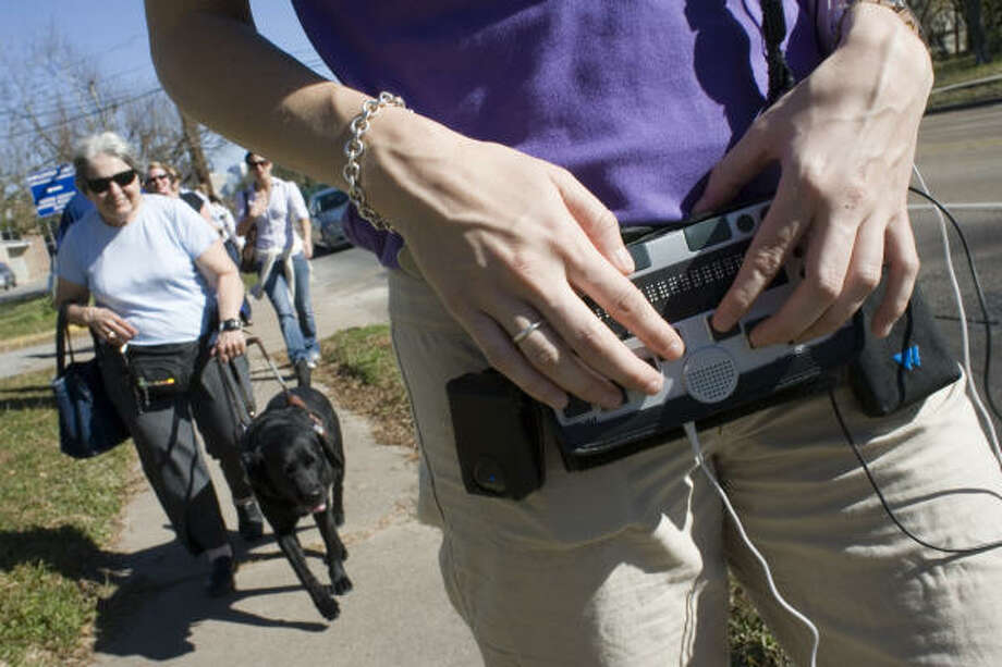 Jamie Adams, right, demonstrates a GPS product for the visually impaired to  Bernice Klepac and her guide dog Niobe. Photo: Eric Kayne, Chronicle