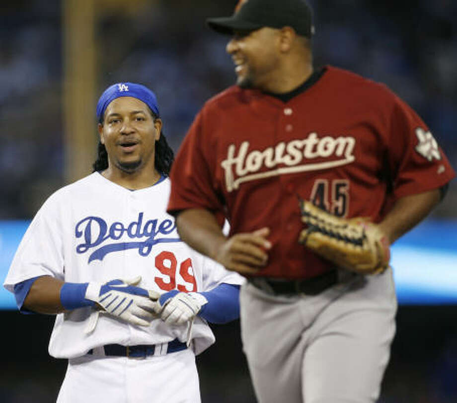 Despite grounding out to end the third inning, the Dodgers' Manny Ramirez, left, still shares a laugh with Astros left fielder Carlos Lee during Saturday's game. Photo: Danny Moloshok, AP