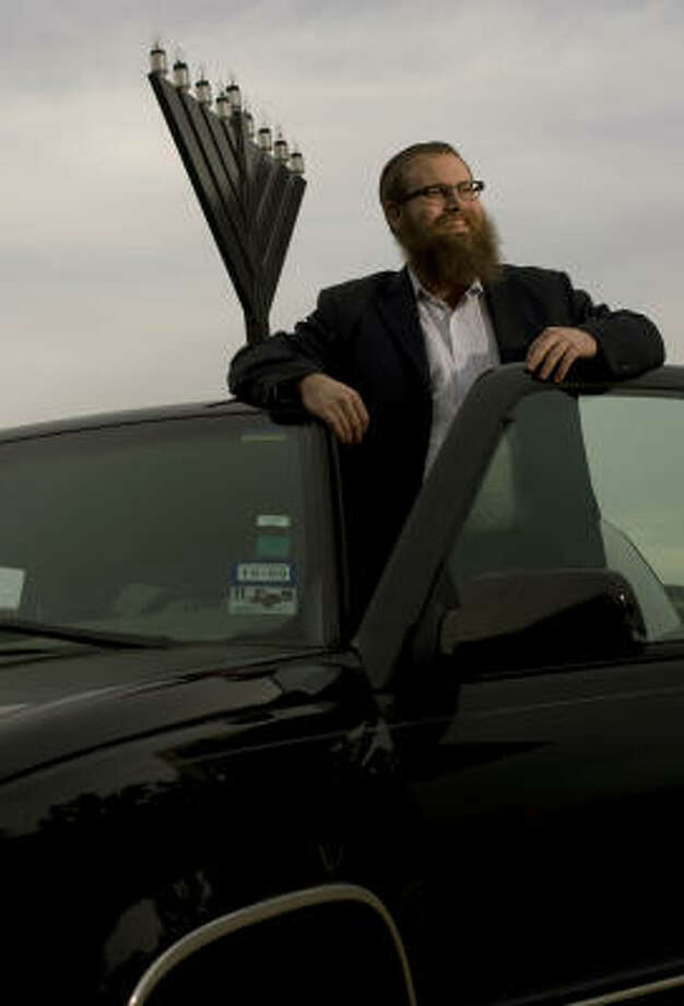 """Rabbi Mendel Traxler stands next to a """"menorah mobile,"""" which he uses to broadcast information about Hanukkah. Photo: Johnny Hanson, Chronicle"""