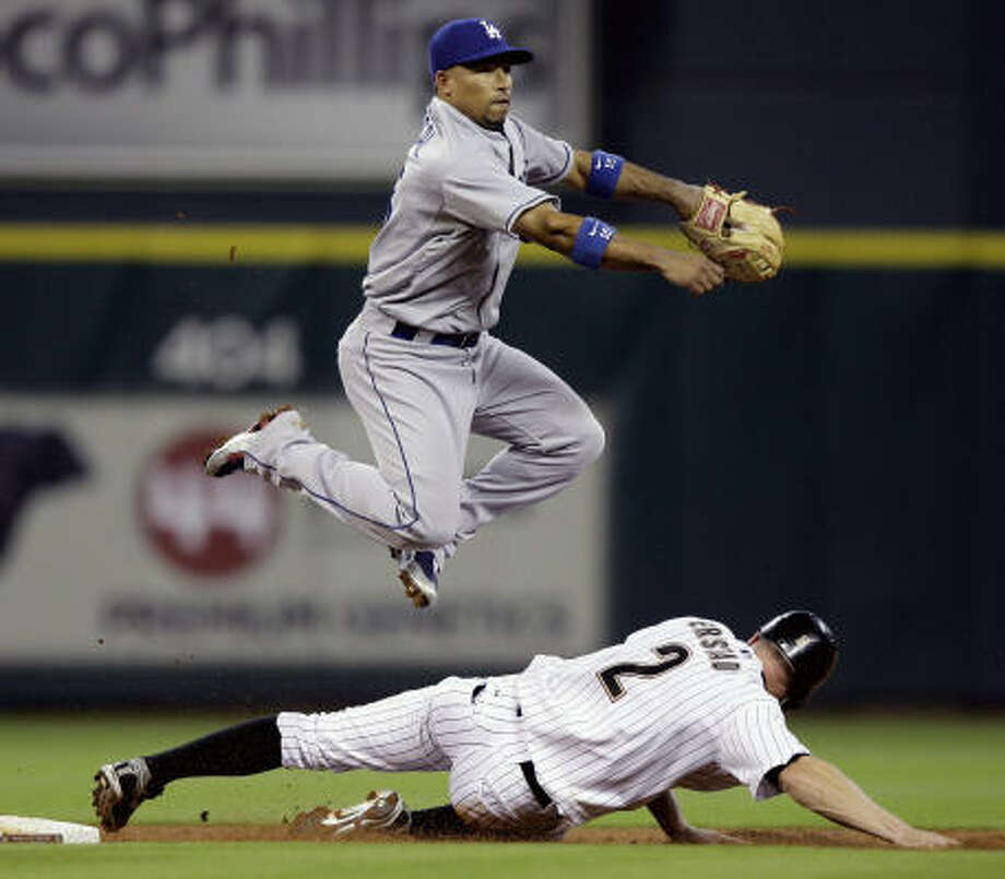Dodgers shortstop Rafael Furcal, top, leaps over Darin Erstad and throws to complete a double play. Photo: David J. Phillip, AP