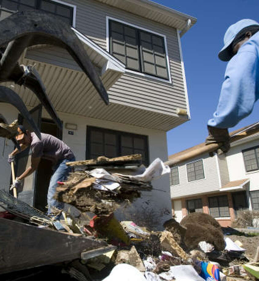 Jose Molina, left, and Jerry Franklin load debris into a front-end loader at the Cedar Terrace Housing Complex in Galveston. The Galveston Housing Authority has decided to renovate two of its sprawling public housing projects and demolish two others. Photo: Eric  Kayne, Chronicle