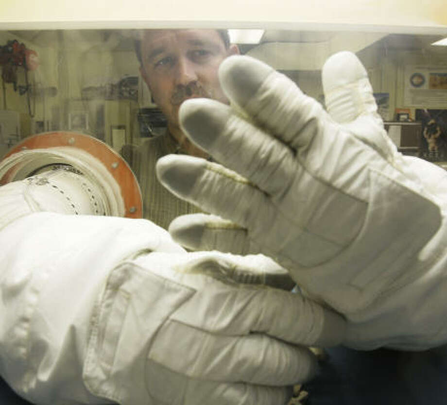 "Johnson Space Center's ""glove box,"" shown by spacewalker John Grunsfeld, is designed to verify the fit and dexterity of an astronaut's spacesuit gloves in a vacuum. Photo: Melissa Phillip, Chronicle"