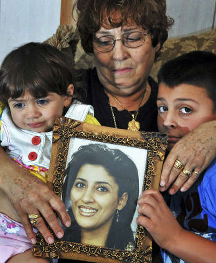A grief stricken Adele Rizk holds a photo of her daughter Diane Rizk McCabe, and Diane's Children, Jenna,2, and Louie,8, at her Troy, NY, home Wednesday afternoon July 22, 2009. Diane Rizk McCabe died 2 years ago after bleeding to death following a Cesarean section delivery of her infant daughter at Albany Medical Center.  (John Carl D'Annibale / Albany Times Union) Photo: John Carl D'Annibale, Albany Times Union