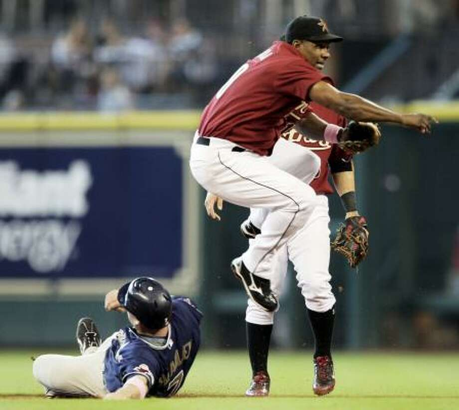 Astros shortstop Miguel Tejada leaps over the slide of Padres left fielder Chase Headley as he relays the throw to first to complete a double play in the second inning. Photo: Bob Levey, AP