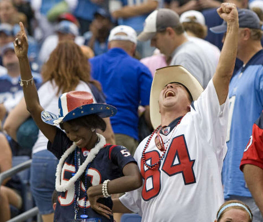 Texans fans Kay Porter, left, and Buzz Thompson celebrate the team's 34-31 victory over the Tennessee Titans. Photo: Brett Coomer, Chronicle