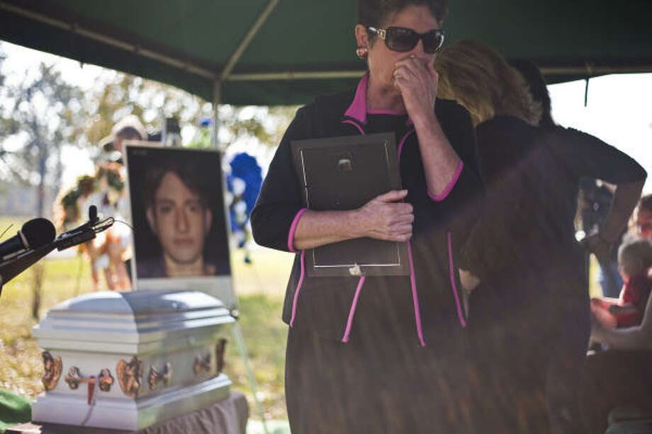 "Cindi Michalk pays her respects Thursday at services for one of 1970s serial killer Dean Corll's unnamed victims. The portrait shows how ""Swimming Suit Boy"" might have looked. Photo: Michael Paulsen, Chronicle"
