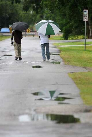 Eugene Tatum, left, and Weldon Brooks catch a pocket of light rain while walking to the Eighth Street bus stop in Beaumont recently. Guiseppe Barranco/The Enterprise