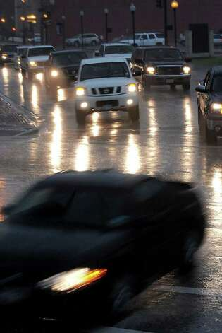 Drivers in downtown Beaumont navigate  wet roads recently.Though it is  definitely is hot in Southeast Texas,  the state's drought inde indicates  the area is the wettest spot in Texas this week. Guiseppe Barranco/The Enterprise