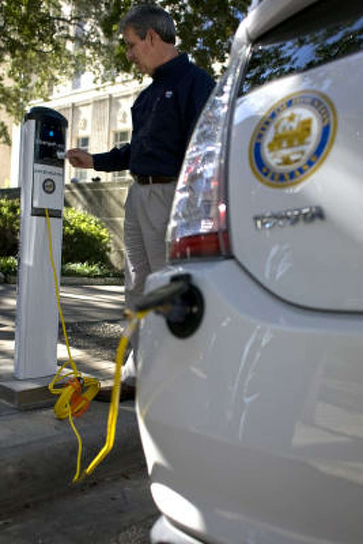 Mike McCabe, Reliant Energy technology manager, tries out the new vehicle charging station outside Houston's City Hall on Tuesday. With Reliant, the city is converting 10 of its hybrids into plug-in vehicles.