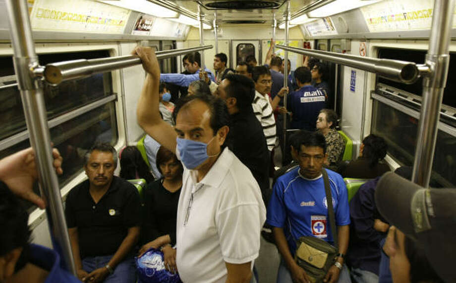 In Mexico City's subway system Saturday, most commuters weren't wearing the protective surgical masks to prevent the spread of swine flu. Officials were urging people to wear the masks in crowds.  Photo: Julio Cortez, Chronicle