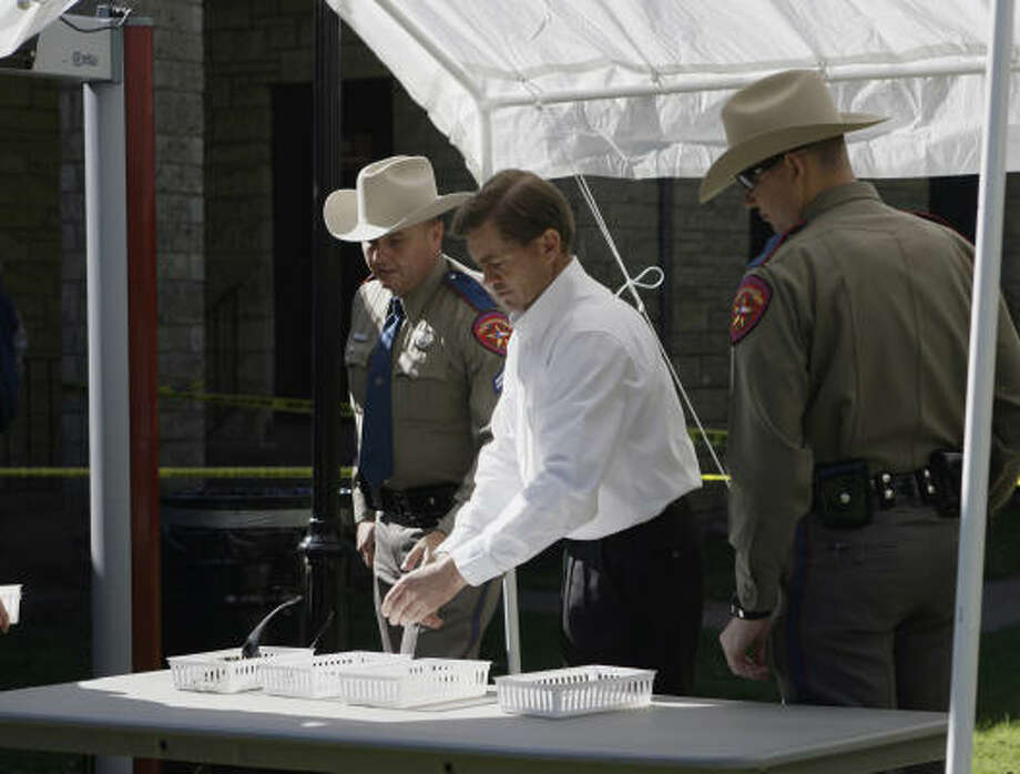 Raymond Jessop, center, the first man to face criminal charges following the raid of a polygamist sect's West Texas ranch, prepares to go through security at the Eldorado courthouse. Photo: Harry Cabluck, Associated Press