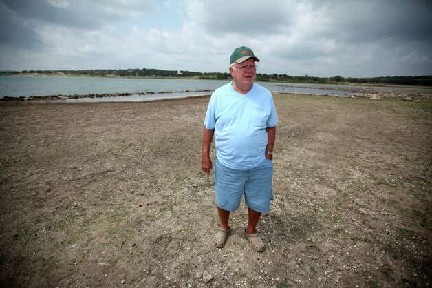 Wilbur George stands in an area that would normally be covered with water at his property on the north side of Canyon Lake on July 22, 2011. Photo: ANDREW BUCKLEY, ANDREW BUCKLEY/abuckley@express-news.net / Copyright: Andrew Buckley