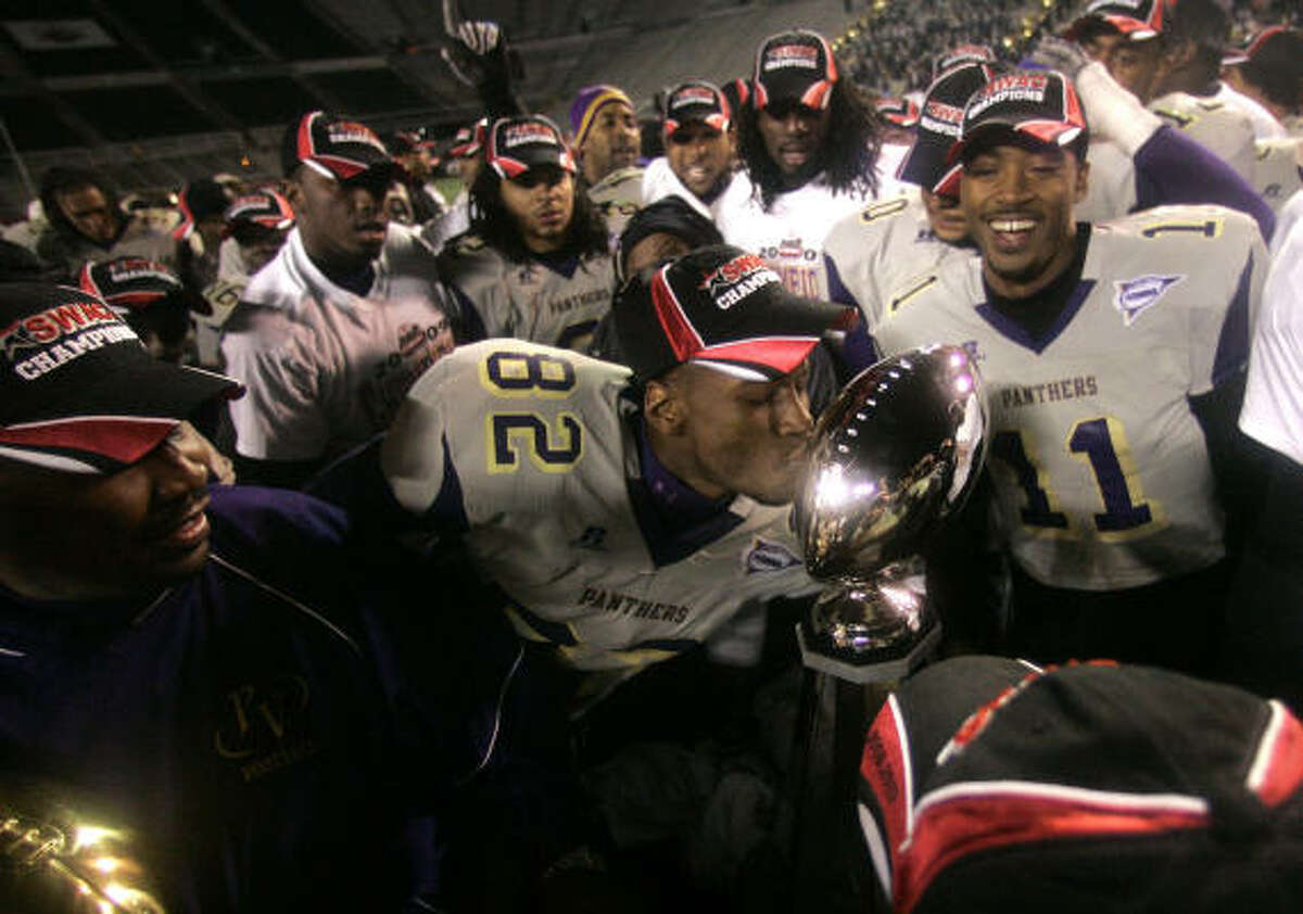 Surrounded by his beaming teammates, Prairie View receiver Gabe Osaze-Ediae (82) plants a kiss on the Eddie Robinson Trophy after the Panthers beat Alabama A&M 30-24 in the SWAC Championship Game on Saturday in Birmingham, Ala.
