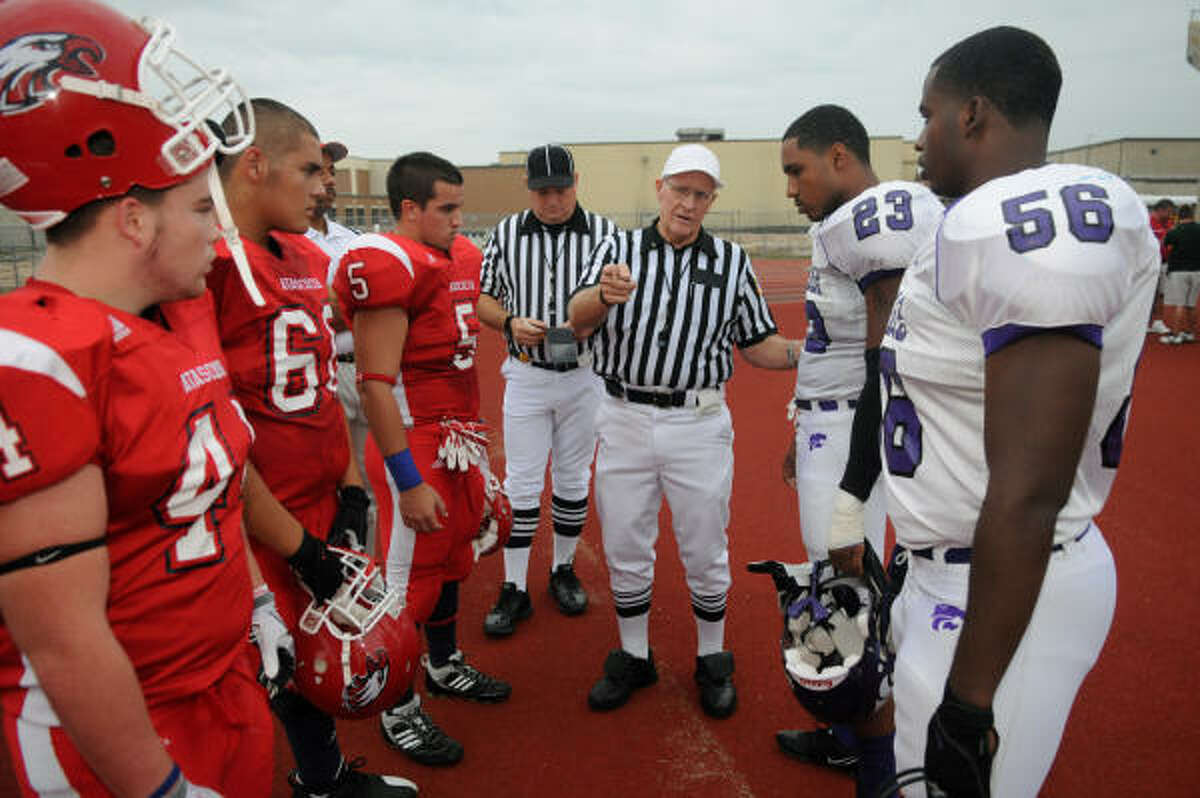 Officials like referee Johnny Bruce of Conroe, instructing the captains from Humble, left, and Atascocita, will be under the control of the UIL next season.