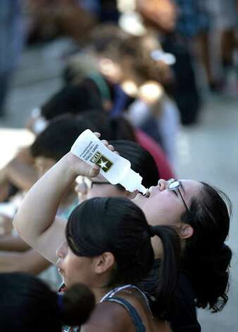 Amanda Herrera drinks from her water bottle during a break at the South San High School Marching Band practice in the school's parking lot, Thursday, August 4, 2011. Photo: BOB OWEN, Bob Owen/rowen@express-news.net / rowen@express-news.net