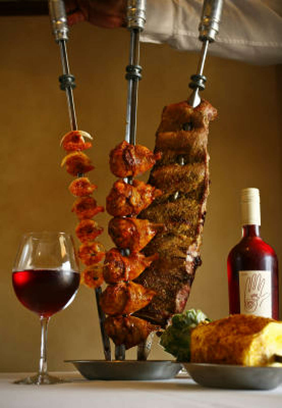 The Angus Grill Brazilian Steakhouse's menu includes shrimp, chicken legs and pork ribs on skewers with fried pineapple, and Crios Malbec Rosé.