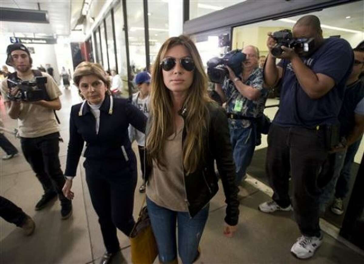 Rachel Uchitel, seen at Los Angeles International Airport on Sunday, has denied having an affair with Tiger Woods. Her attorney, Gloria Allred, is at left.