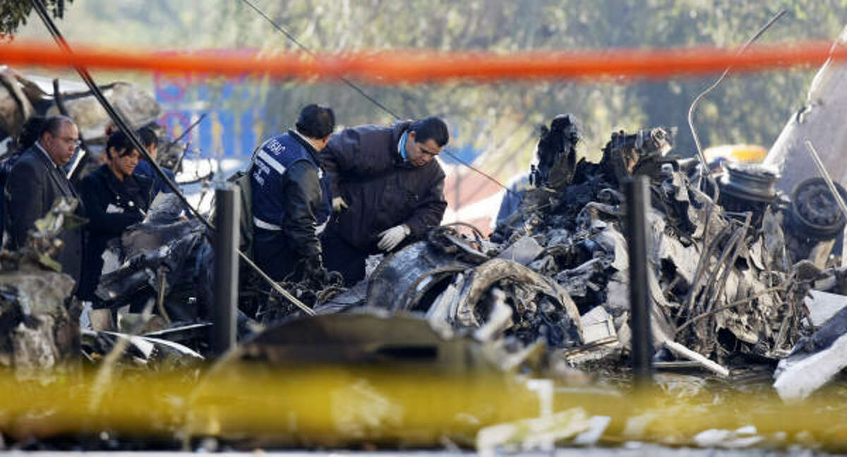 Forensics workers investigate the Nov. 5 plane crash in Mexico City that killed drug czar Jose Luis Santiago Vasconcelos and Interior Secretary Juan Camilo Mourino.