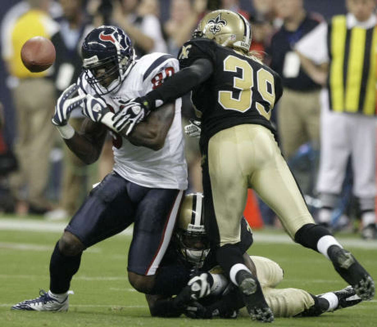 Texans wide receiver Andre Johnson fumbles as he is hit by Saints cornerback Tracy Porter (22) and safety Chris Reis (39).