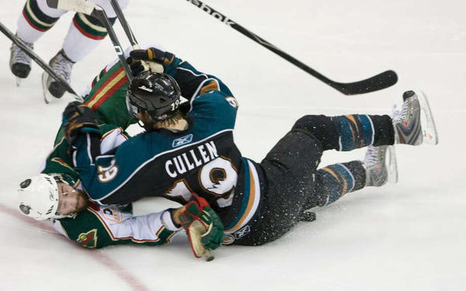 Aeros defender Clayton Stoner, left, gets knocked down by Manitoba Moose center Mark Cullen during the third period. Photo: Nick De La Torre, Chronicle