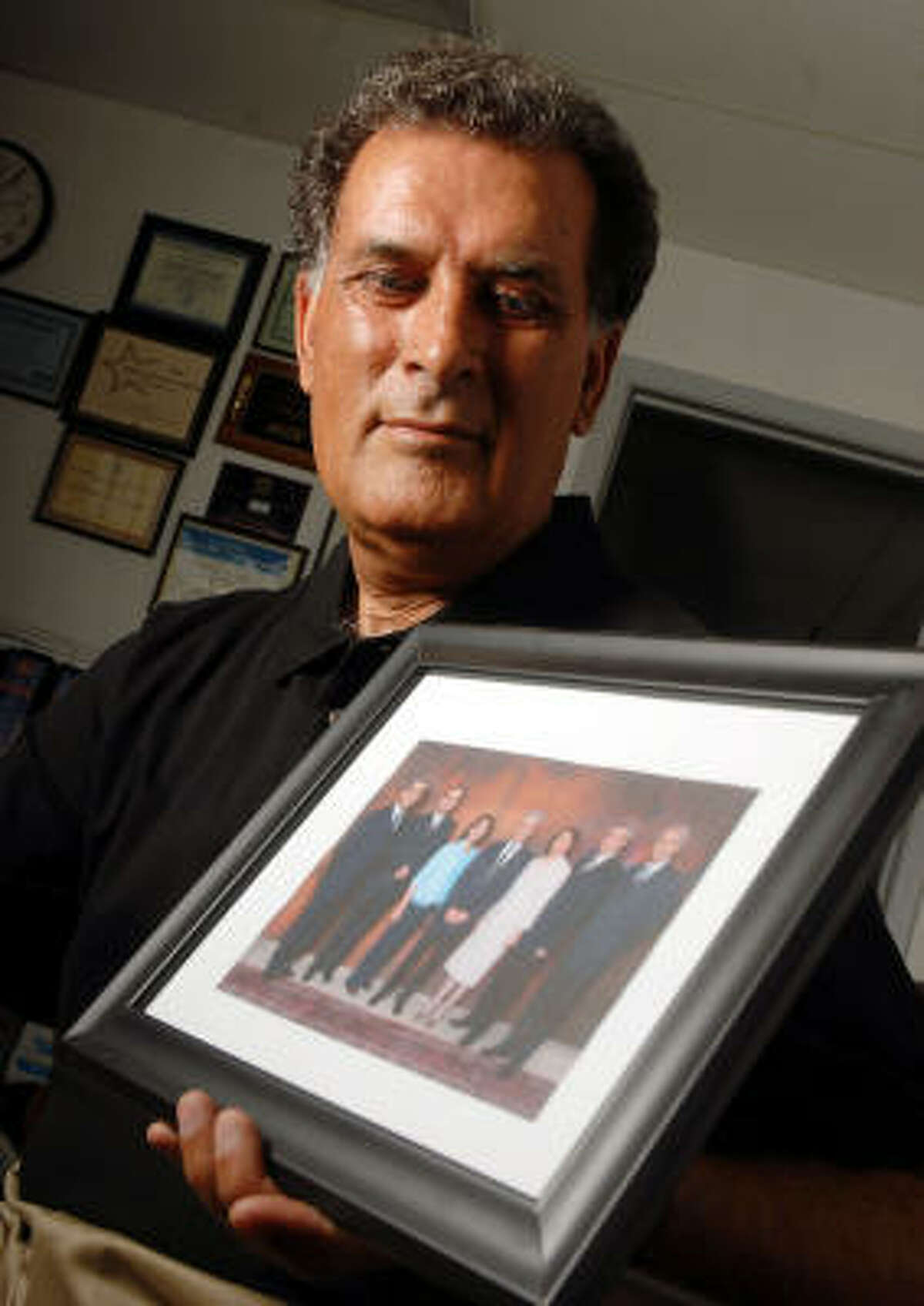 Kamal Khanjani's brother Jamaloddin and six other Baha'i members, seen in the photo he's holding, on Saturday will go on trial for their lives in Iran.