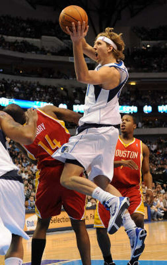 Mavericks forward Dirk Nowitzki runs into Rockets forward Carl Landry, a collision that ended the night for both players. Photo: Ronald Martinez, Getty Images