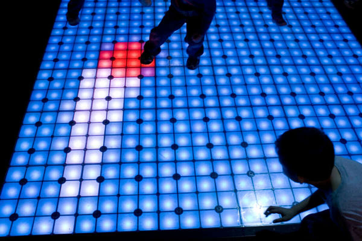 Children play an electronic game of dodge ball on a lighted floor at an event celebrating the expansion of the Houston Children's Museum on Saturday.