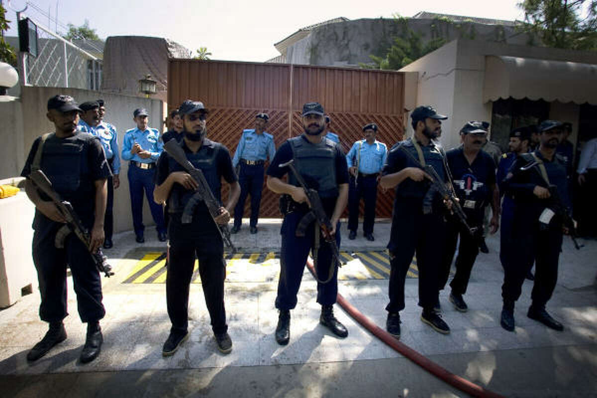 Police commandos stand guard at the main entry gate of a U.N. food agency's office after a suicide bombing in Islamabad, Pakistan, killed at least five people.