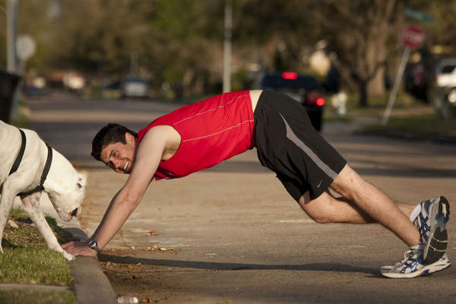 Chris Bolio gets loose with his dog, Ajax, before an evening run near his Timbergrove home. Photo: Smiley N. Pool, Houston Chronicle