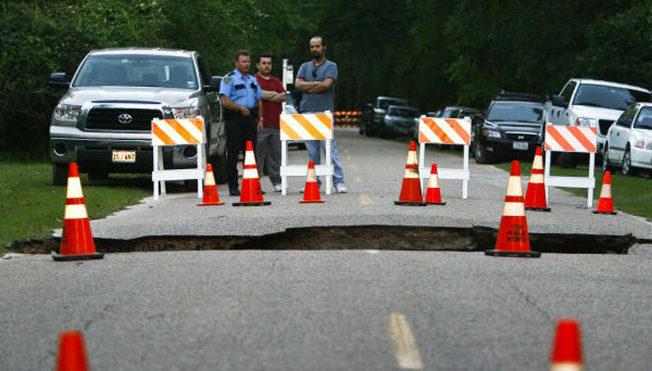 Onlookers survey the scene on the road leading to River Grove Park on Sunday. Photo: Michael Paulsen, Chronicle