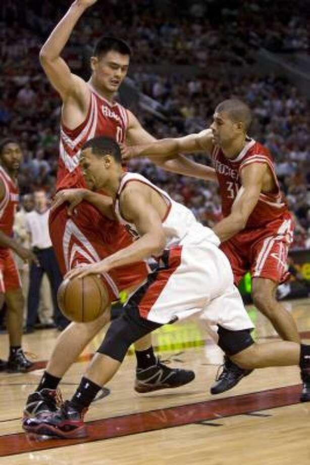 Blazers guard Brandon Roy, middle, dribbles inside against Houston Rockets center Yao Ming and Shane Battier during the first half. Photo: Don Ryan, AP