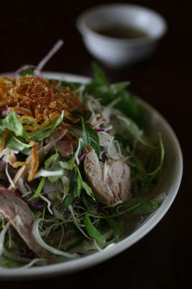 In goi vit, Lime, pepper, sugar, ginger and fish sauce made a garlicky dressing to splash over a shredded duck salad laced with slivered red onion and freshened with leaves of cilantro and rau. Photo: Mayra Beltran, Houston Chronicle