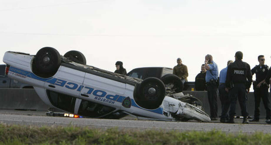 Friendswood and Houston police direct traffic around a Houston police cruiser that flipped during Monday's chase on Interstate 45. Photo: Nick De La Torre, CHRONICLE