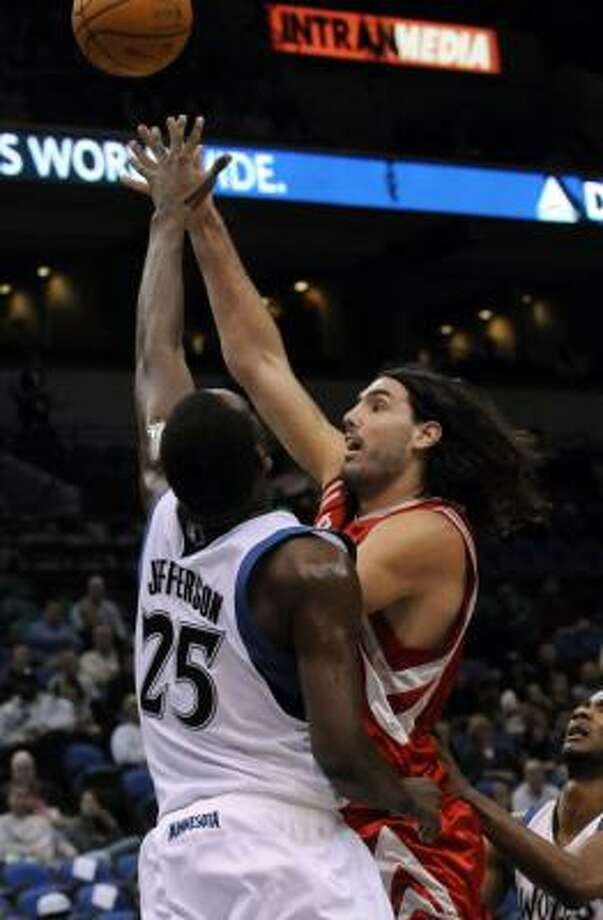 Rockets forward Luis Scola shoots over the Timberwolves' Al Jefferson in the first quarter. Photo: Jim Mone, AP